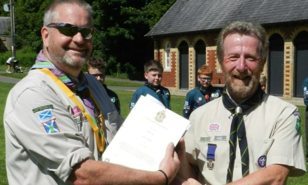 Dougie Simmers presenting Keith Millar with the Silver Cross for his heroic efforts