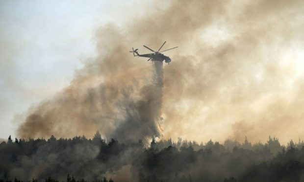 An helicopter drops water over a fire in Varibobi area, northern Athens, Greece, Wednesday, Aug. 4, 2021. Firefighting planes were resuming operation at first light Wednesday to tackle a major forest fire on the northern outskirts of Athens which raced into residential areas the previous day, forcing thousands to flee their homes amid Greece's worst heatwave in decades. AP Photo/Thanassis Stavrakis