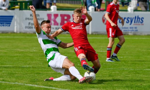 Buckie Thistle's Sam Pugh and Connor Barron of Aberdeen battle for the ball. Picture by Kenny Elrick