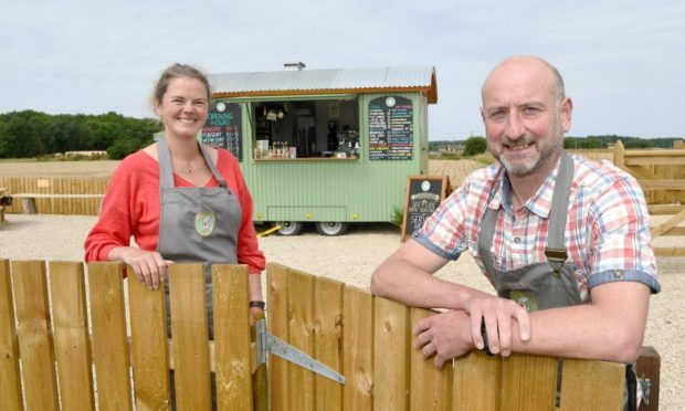 Lady Caroline and Sir Ed Dunbar outside their Kula Coffee Hut.