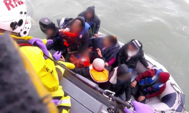 A dinghy full of migrants being rescued by the RNLI in the English Channel (Photo: PA)