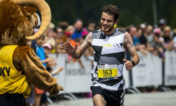 Robbie Simpson of Britain celebrates as he crosses the finish line of the men's category during the 48th Sierre-Zinal long distance mountain race in Zinal, Switzerland, 7 August 2021.