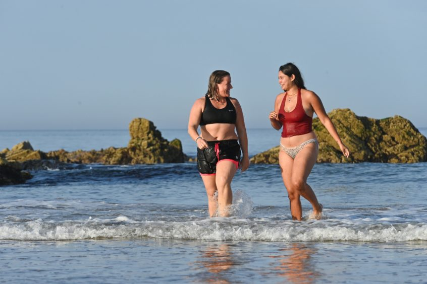 Zahra Abdul from Tarves (red) and Gemma Emslie from Aberdeen are pictured at Cullen beach, Moray on the hottest day of September in 100 years, Pictures by Jason Hedges.
