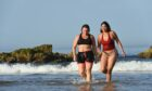 Zahra Abdul from Tarves (red) and Gemma Emslie from Aberdeen are pictured at Cullen beach, Moray on the hottest day of September in 100 years. Pictures by Jason Hedges.