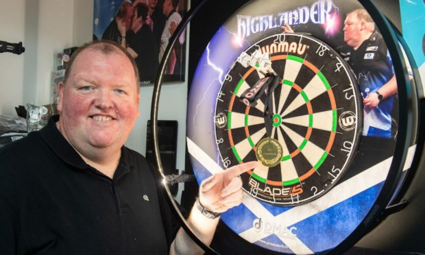 John Henderson at home in Huntly with his World Cup of Darts medal