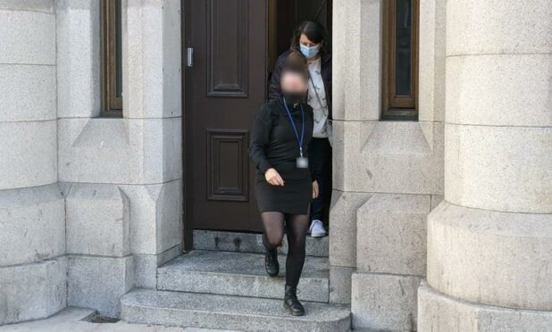 Joanne Cresswell (back) being escorted from Aberdeen Sheriff Court by a social worker.