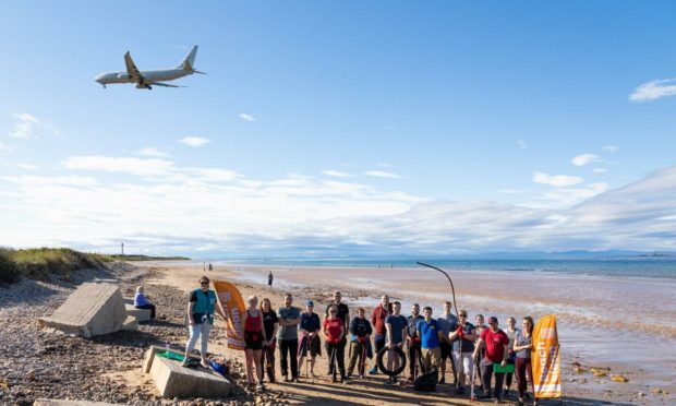 Volunteers from RAF Lossiemouth clearing their local beach, with a Poseidon aircraft flying overhead. Photo credit: RAF Lossiemouth.