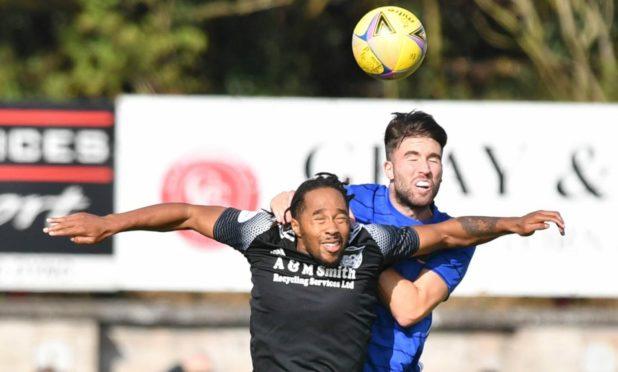 Cove Rangers defender Morgyn Neill challenges Peterhead's Niah Payne.