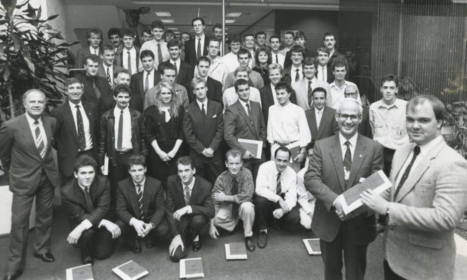 Fifty successful students from throughout Scotland and as far south as Norfolk look on as Shell Expro director of operations Ian Henderson presents Kevin Barrie, Macduff, with his Shell Expro Technician Scheme graduation certificate at Shell's Tullos HQ in 1998.