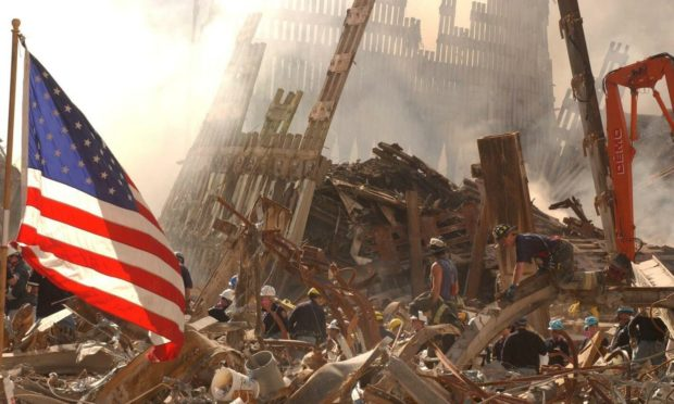 Rescue workers climb over and dig through piles of rubble from the destroyed World Trade Center as the American flag billows over the debris.