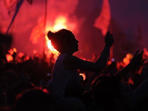 Flares in the crowd as the Rolling Stones perform on the Pyramid Stage during the Glastonbury 2013 Festival at Pilton Farm, Somerset.