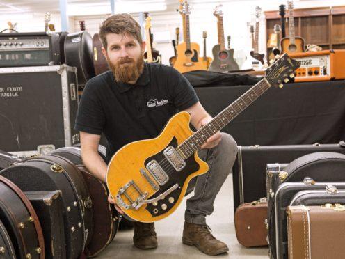 Auctioneer Luke Hobbs with George Harrison's Maton guitar (Gardiner Houlgate/PA)