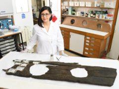 Conservator Luisa Duarte with the 12th century triple toilet seat (Matt Crossick/PA)