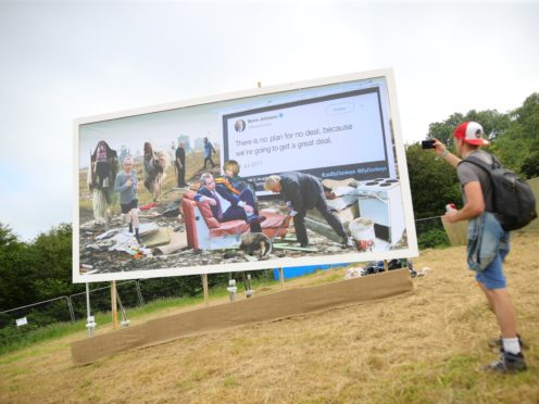 A billboard is unveiled on the first day of the Glastonbury Festival (Aaron Chown/PA)