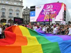 Members of the public watch during the Pride in London Parade (Dominic Lipinski/PA)