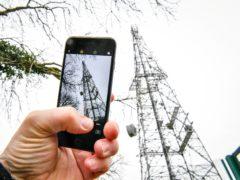 A mobile phone next to a telecoms mast (PA)