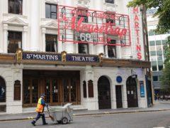 A street cleaner walks past the closed St Martin's Lane theatre (Dominic Lipinski/PA)
