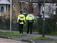 A Sussex police officer and a Community Support Officer walk along a street in Crawley, Sussex (Steve Parsons/PA)