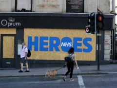 People walk past a boarded up shop in Glasgow with a tribute to the NHS (Andrew Milligan/PA)