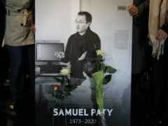 People hold a photo of the history teacher Samuel Paty during a memorial march on Tuesday (Lewis Joly/AP)
