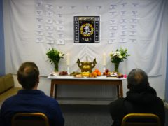 Visitors to the memorial shrine at the Hackney Chinese Community Services mark the first anniversary of the Essex container tragedy (Kirsty O'Connor/PA)