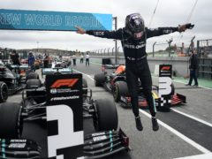 Lewis Hamilton of Britain jumps out of his car after his record breaking 92nd win at the Formula One Portuguese Grand Prix (Jorge Guerrero/Pool/AP)