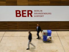 People walk in front of a sign at the new Berlin Brandenburg Airport Willy Brandt (Markus Schreiber/AP)