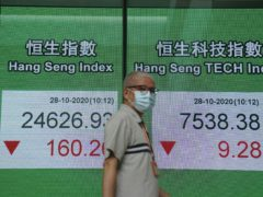 A man wearing a face mask walks past a bank's electronic board showing the Hong Kong share index in Hong Kong (Kin Cheung/AP)