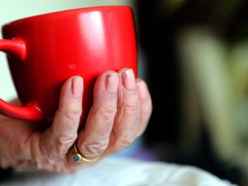 An elderly woman holding a cup of tea at home (Peter Byrne/PA)