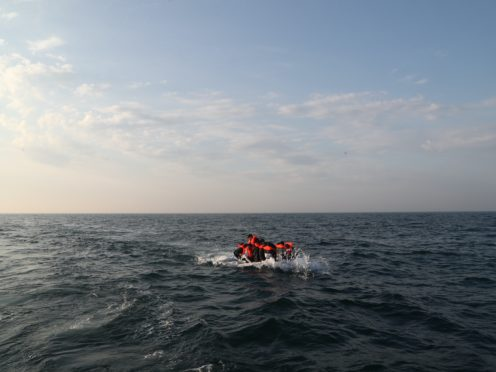 A group of people thought to be migrants crossing the Channel in a small boat headed in the direction of England (PA)