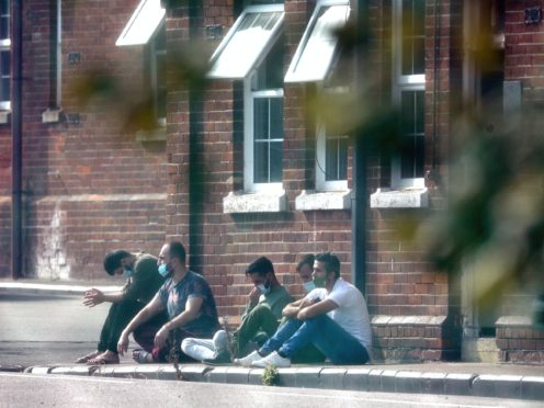 A group of men, thought to be migrants, sit outside in the sunshine after arriving yesterday night at Napier Barracks in Folkestone, Kent. Migrants will be housed in the military barracks from this week while their asylum claims are processed.
