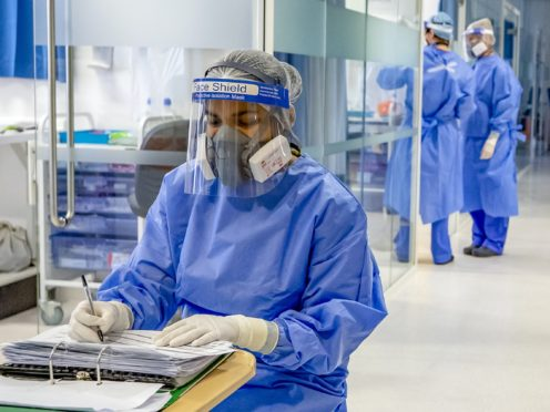 Health workers wearing full personal protective equipment on an intensive care unit (Peter Byrne/PA)