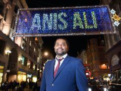 NHS volunteer responder Anis Ali looks on as his name appears in lights above Oxford Street, London (Matt Crossick/PA Wire)