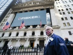 Stock trader Thomas Ferrigno arrives to work at the New York Stock Exchange, as world markets soared higher (AP Photo/Mark Lennihan)