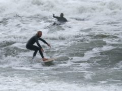 People surfing in the sea off Boscombe beach in Dorset (Andrew Matthews/PA)