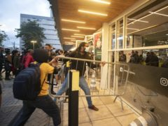 Demonstrators use a crowd control barrier to smash into the entrance of a Carrefour supermarket during a protest against the murder of black man Joao Alberto Silveira Freitas (Andre Penner/AP)