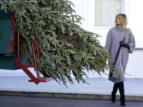 First lady Melania Trump walks around the 2020 official White House Christmas tree after it arrived at the White House in Washington, Monday, Nov. 23, 2020. This year's tree is an 18.5-foot Fraser Fir, selected and cut from Dan and Bryan Trees in Shepherdstown, W.Va. (AP Photo/Andrew Harnik)