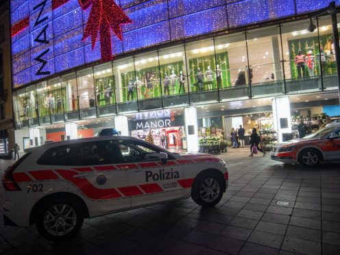 A police car in the area where a stabbing occurred in a department store, in Lugano, Switzerland, Tuesday, Nov. 24, 2020. Swiss authorities are investigating as a possible terror attack the stabbing of two women in an department store in the southern city of Lugano, and a suspect has been arrested. Officials said one of the victims sustained serious but not life-threatening injuries, while the other sustained minor injuries. (Ti-Press/Keystone via AP)