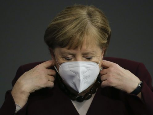 German Chancellor Angela Merkel adjusts her face mask as she arrives for a parliament session about German government's policies to combat the spread of the coronavirus (Markus Schreiber/AP)
