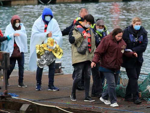 A group of people thought to be migrants are helped by Border Force officers as they are brought into Dover in Kent following a small boat incident in the Channel (Gareth Fuller/PA