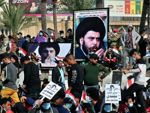 Followers of Shiite cleric Muqtada al-Sadr, in the posters, gather in Tahrir Square, Baghdad (Khalid Mohammed/AP)