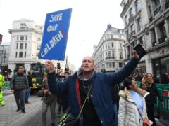 Demonstrators during an anti-lockdown protest at Oxford Circus (Victoria Jones/PA)