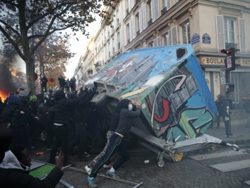 Youths overturn a construction hut during a demonstration against a security law that would restrict sharing images of police, Saturday, Nov. 28, 2020 in Paris. Civil liberties groups and journalists are concerned that the measure will stymie press freedoms and allow police brutality to go undiscovered and unpunished. The cause has gained fresh impetus in recent days after footage emerged of French police officers beating up a Black man, triggering a nationwide outcry. (AP Photo/Francois Mori)
