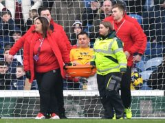 Tom Heaton (centre) is carried off after hurting his knee in January (Anthony Devlin/PA)