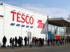 People queue outside a Tesco Extra store (Nick Potts/PA)