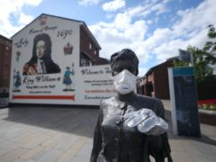 A statue by artist Ross Wilson entitled Mother Daughter Sister, celebrating female identity and culture, in Sandy Row Belfast is adorned with a mask and disposable gloves (Niall Carson/PA)