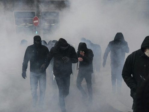 Protesters walk through the tear gas during a demonstration in Lyon (AP)