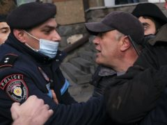 A police officer tries to detain demonstrators during a rally demanding the resignation of Armenia's PM (AP/Hrant Khachatryan)