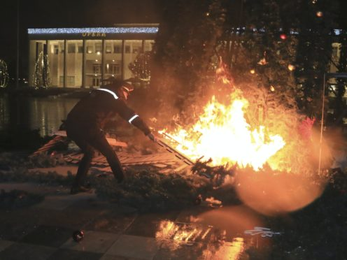 A Christmas tree on fire near the Prime's Minister office during clashes in Tirana, Albania (AP/Hektor Pustina)