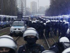 Police in riot gear block the path of anti-government protesters (Czarek Sokolowski/AP)